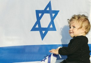 A baby sits in front of an Israeli flag. (photo credit:MARC ISRAEL SELLEM/THE JERUSALEM POST)
